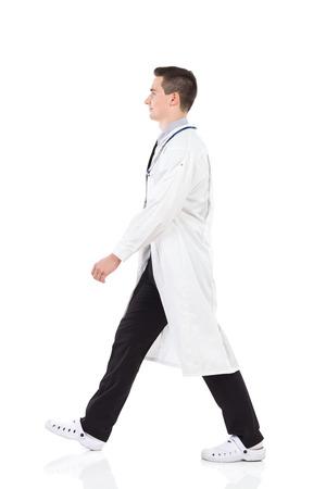 Walking young male doctor. Full length studio shot isolated on white. Standard-Bild