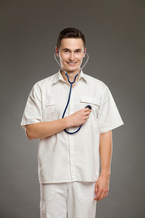 beating: Portrait of a smiling male doctor using stethoscope and listening his heart beating. Three quarter length studio shot on gray background.