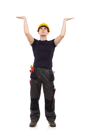 acting: Manual worker acting holding something above his head. Full length studio shot isolated on white. Stock Photo