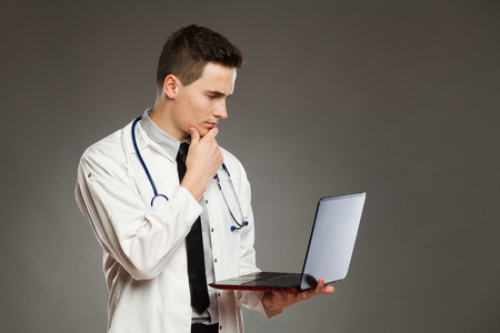 waist shot: Portrait of a thinking doctor holding laptop and reading. Waist up studio shot on gray background.