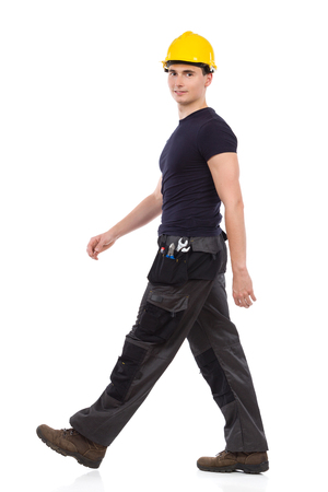 Manual worker walking and looking at camera. Full length studio shot isolated on white. Stock Photo