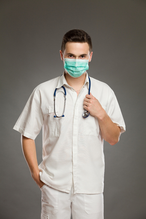 three quarter: Portrait of a male doctor wearing surgical mask. Three quarter length studio shot on gray background. Stock Photo