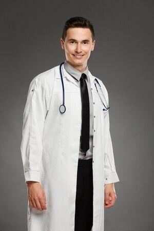 three quarter length: Portrait of a male doctor. Three quarter length studio shot on gray background.
