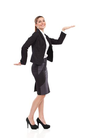 businesswoman skirt: Side view of smiling and walking businesswoman in black suit, mini skirt and high heels. Full length studio shot isolated on white. Stock Photo