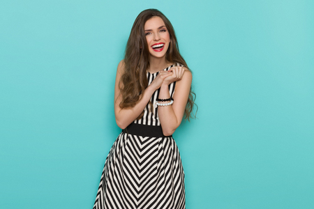 Excited attractive woman in black and white striped dress looking at camera and laughing, Three quarter length studio shot on turquoise background.