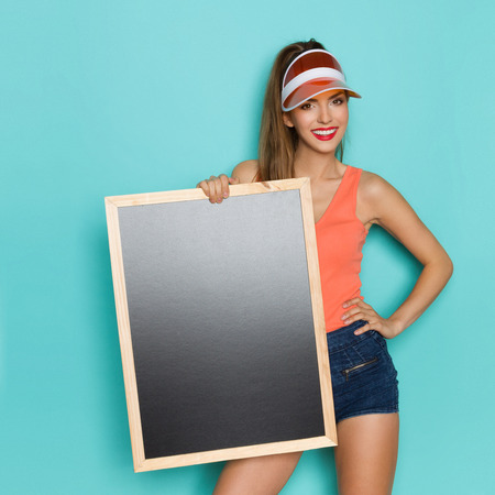 visor: Smiling young woman in orange shirt, jeans shorts and sun visor holding blackboard and looking at camera.Three quarter length studio shot on turquoise background.