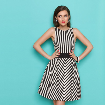 Smiling elegant woman in black and white striped dress posing with hands on hip and looking away, Three quarter length studio shot on turquoise background. Stockfoto