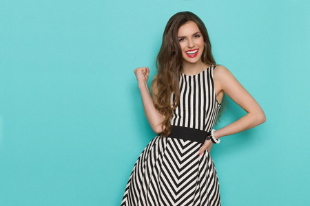 Smiling girl in black and white striped dress posing with fist raised and looking at camera, Three quarter length studio shot on turquoise background.