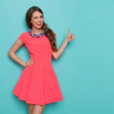 ピンクのミニドレスに親指を表示とウインクの美しい若い女性の笑みを浮かべてください。4 分の 3 の長さスタジオは、背景色が水色の撮影。 写真素材