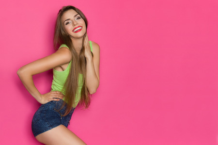 three quarter length: Smiling young woman in lime green shirt and jeans shorts posing with hand on hip and looking at camera. Three quarter length studio shot on pink background. Stock Photo