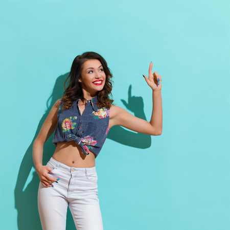 three quarter length: Smiling young woman looking up and pointing. Three quarter length studio shot on teal background. Stock Photo