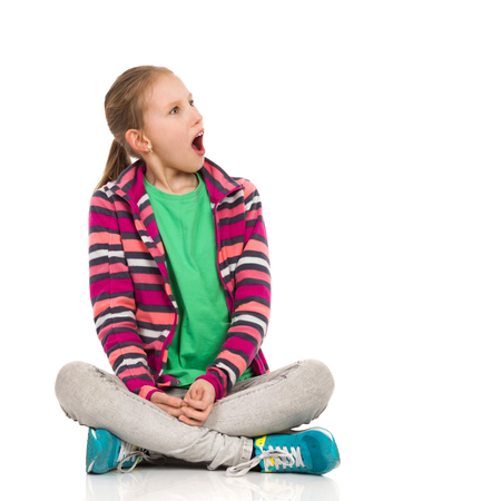 disgusted: Shocked blond girl in striped fleece blouse, jeans and sneakers sitting on floor with legs crossed and looking away. Full length studio shot isolated on white. Stock Photo