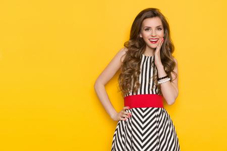 Glimlachende mooie jonge vrouw in zwart-wit gestreepte jurk poseren met de hand op de kin en wegkijken. Drie kwart lengte studio-opname op gele achtergrond.