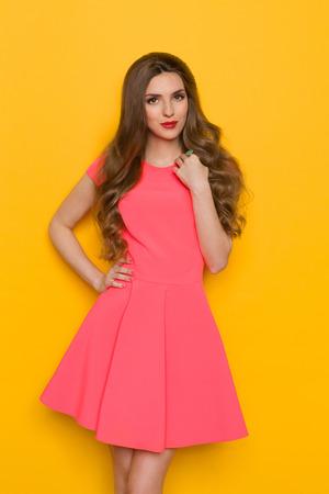 Hermosa mujer joven con el pelo rizado largo y castaño en el vestido rosa de mini presenta con la mano en la cadera y mirando a la cámara. Tres cuartos de longitud estudio disparó sobre fondo amarillo. Foto de archivo