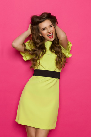 Shouting young woman in lime green dress holding head in hands. Three quarter length studio shot on pink background. Standard-Bild