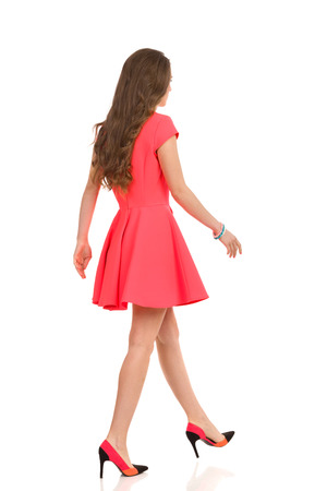 mini dress: Elegant woman in pink mini dress and high heels walking, Rear side view. Full length studio shot isolated on white.