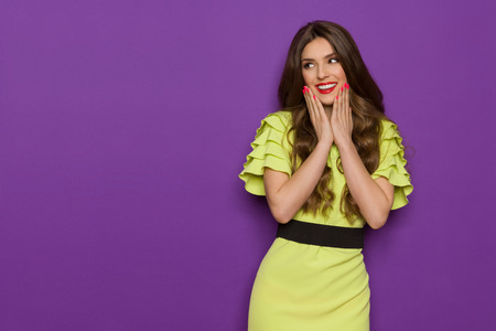 three quarter length: Smiling beautiful young woman in lime green dress posing with hands on chin and looking away. Three quarter length studio shot on purple background.