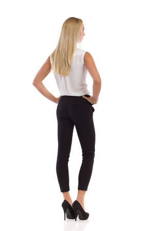 platinum hair: Young blond woman in white shirt, black pants, and high heels standing with hands on hip. Rear view. Full length studio shot isolated on white. Stock Photo