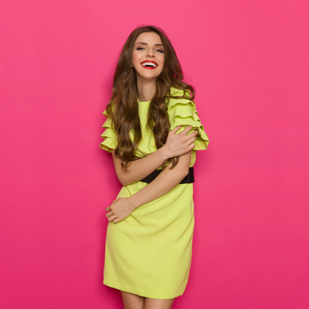 three quarter length: Laughing young woman in lime green dress. Three quarter length studio shot on pink background.