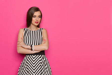 Beautiful young woman in striped dress posing with arms crossed and looking away. Three quarter length studio shot on pink background.