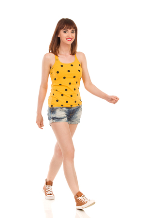 Young smiling woman in yellow dotted shirt, jeans shorts and brown sneakers walking. Full length studio shot isolated on white.