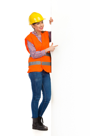 reflective vest: Smiling young woman in yellow hardhat, orange reflective vest and lumberjack shirt standing behind big white banner and pointing. Full length studio shot isolated on white.