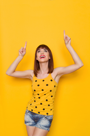 arms above head: Young ecstatic woman in yellow dotted shirt, jeans shorts looking up and pointing. Three quarter length studio shot on yellow background. Stock Photo