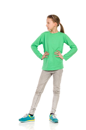 legs apart: Cheerful young girl in green blouse, jeans and sneakers standing with legs apart, posing with hands on hip and looking away. Full length studio shot isolated on white.