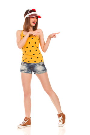 legs apart: Young woman in yellow dotted shirt, jeans shorts and brown sneakers standing with legs apart, pointing and talking. Full length studio shot isolated on white.