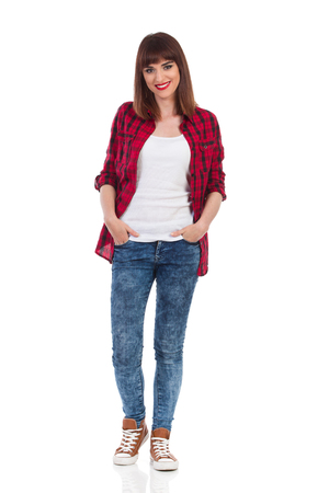lumberjack shirt: Smiling young woman in red lumberjack shirt, jeans and brown sneakers standing with hands in pocket and looking at camera. Full length studio shot isolated on white.