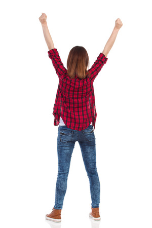 cheer full: Smiling young woman in red lumberjack shirt, jeans and brown sneakers standing with arms raised. Rear view. Full length studio shot isolated on white.