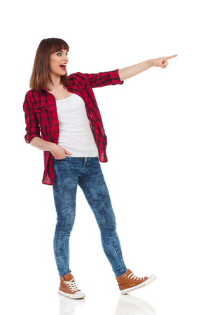 apart: Shouting young woman in red lumberjack shirt, jeans and brown sneakers standing with legs apart, pointing and looking away. Full length studio shot isolated on white.