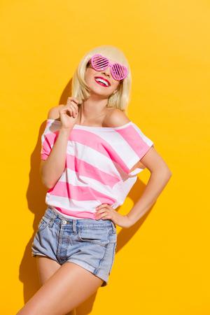 three quarter length: Beautiful blond girl in pink sunglasses smiling. Three quarter length studio shot on yellow background.