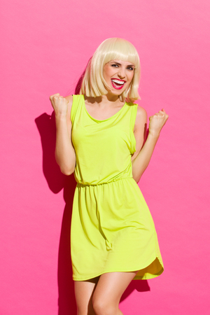 three quarter length: Smiling blond girl in lime dress gesturing success with fists raised in the air. Three quarter length studio shot on pink background.