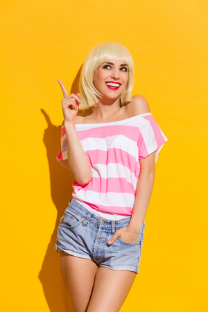 woman posing: Smiling beautiful blonde young woman pointing up. Three quarter length studio shot on yellow background. Stock Photo