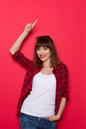 waist shot: Young smiling girl in red lumberjack shirt pointing up. Waist up studio shot on red background.