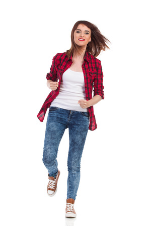 towards: Young woman in red lumberjack shirt, jeans and brown sneakers running towards the camera. Full length studio shot isolated on white. Stock Photo