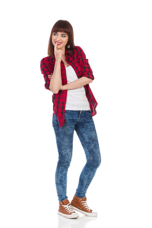 observe: Smiling young woman in red lumberjack shirt, jeans and brown sneakers standing and observe something. Full length studio shot isolated on white.