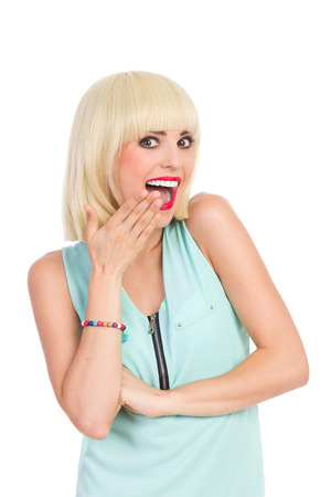 adult oops: Beautiful blonde girl shouting and holding hand on mouth. Waist up studio shot isolated on white.