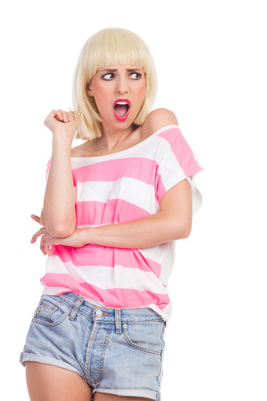 three quarter length: Grimacing blonde young woman looking away. Three quarter length studio shot isolated on white.