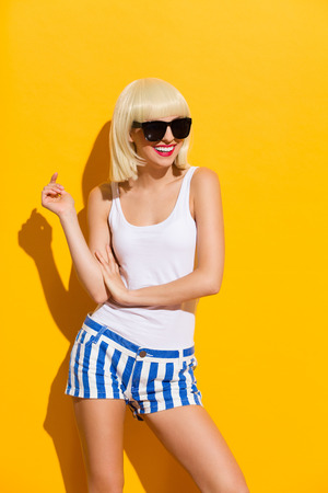 three quarter length: Smiling beautiful blonde young woman in black sunglasses. Three quarter length studio shot on yellow background.
