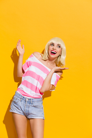 three quarter: Laughing blonde spread her hands and looking up. Three quarter length studio shot on yellow background.