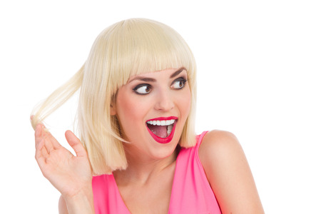 Close up of a ecstatic beautiful blonde young woman holding piece of her hair. Head and shoulders studio shot isolated on white.