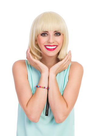 chin on hands: Close up of a smiling beautiful blond young woman holding hands beneath chin. Waist up studio shot isolated on white.