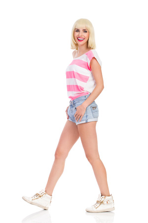 striding: Smiling blonde young woman walking and looking at camera. Full length studio shot isolated on white.