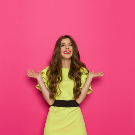 three quarter length: Laughing young woman in lime green dress posing with arms outstretched. Three quarter length studio shot on pink background.