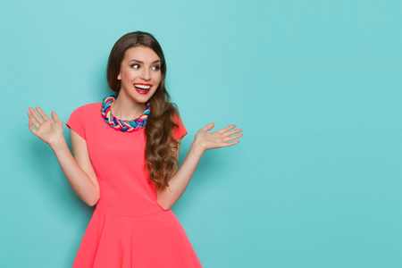 Laughing beautiful young woman in pink mini dress standing with arms outstretched and looking away. Three quarter length studio shot on turquoise background. Archivio Fotografico