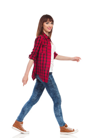 Woman in red lumberjack shirt, jeans and brown sneakers walking and looking at camera. Side view. Full length studio shot isolated on white. Stock Photo