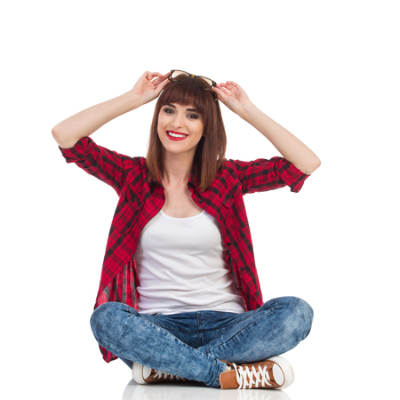 lumberjack shirt: Smiling young woman in red lumberjack shirt, jeans and brown sneakers sitting on a floor with legs crossed, holding sunglasses on a head and looking at camera. Full length studio shot isolated on white.