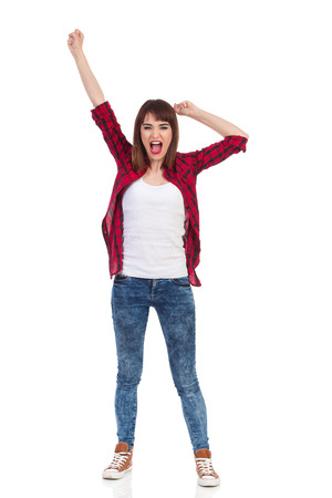 lumberjack shirt: Shouting young woman in red lumberjack shirt, jeans and brown sneakers standing with legs apart and looking at camera. Full length studio shot isolated on white. Stock Photo